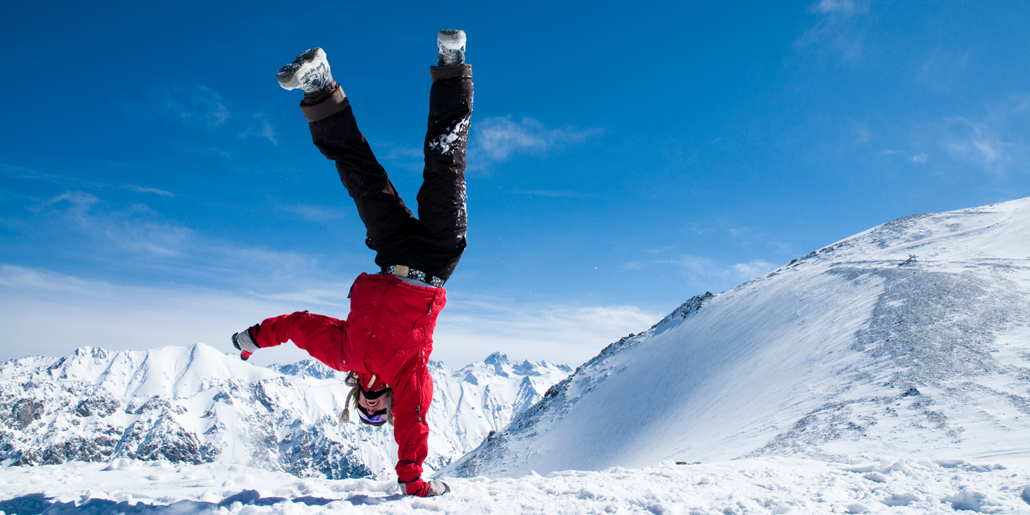 Someone doing a one-handed handstand high in the snowy mountains